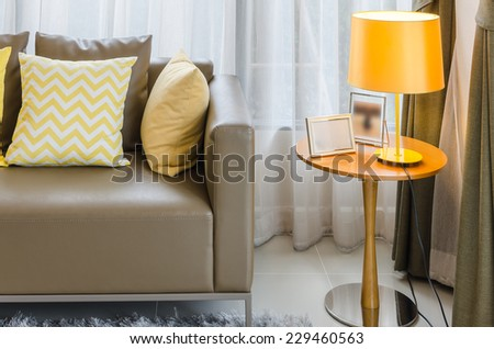 brown sofa with yellow pillows and lamp in living room - stock photo