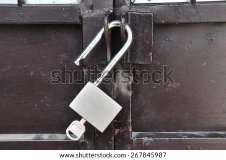 Brown steel door with padlock, unlocked. - stock photo