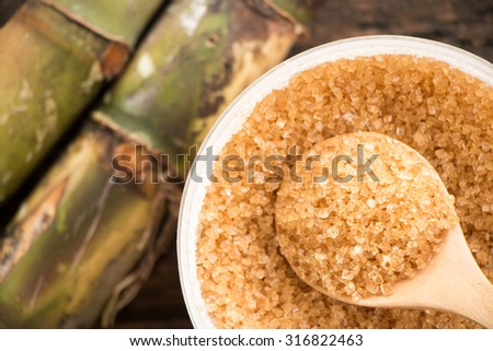 Brown sugar close-up on wooden spoon with Sugar cane - stock photo