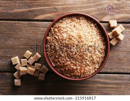 Brown sugar cubes and crystal sugar in bowl on wooden background - stock photo
