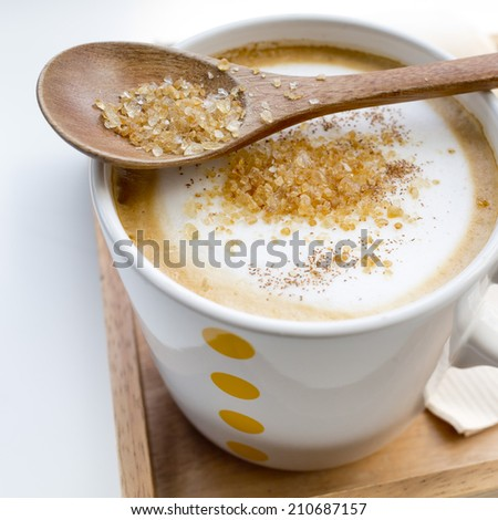 Brown sugar on a spoon and a cup of coffee Cappuccino - stock photo