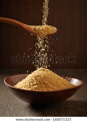 Brown Sugar pouring from a spoon to a bowl - stock photo