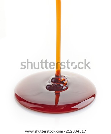 brown sugar syrup pouring isolated on a white background - stock photo