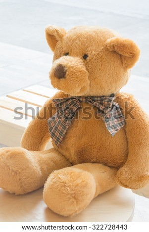 Brown teddy bear sitting on wooden chair , selective focus point and soft light. - stock photo