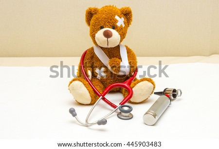 Brown teddy bear with bandages and broken hand in pediatrician's office - stock photo
