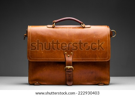 Brown Vintage leather briefcase with strap and brass buckle,  - stock photo
