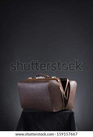 Brown vintage valise on a dark background. - stock photo