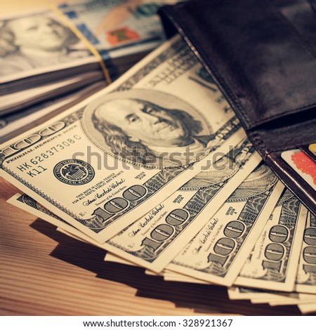 Brown Wallet with credit cards and one hundred dollars banknotes. Shallow depth of field. Retro vintage filtered hipster color image. Creative business finance making money concept . - stock photo
