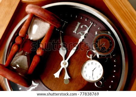 Brown watch, clock and hourglass. Still-life with different watches - stock photo