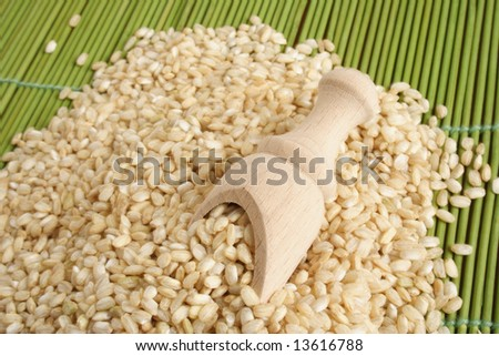 Brown wholegrain rice for cooking on a mat - stock photo