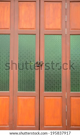 Brown wood and green glass door - stock photo