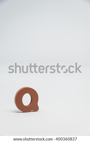 Brown Wooden alphabet Q with white background in Vertical view - stock photo