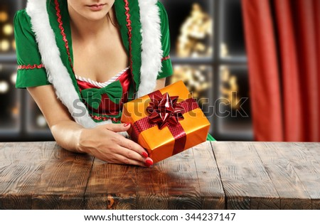 brown wooden table and box of xmas time in hands  - stock photo