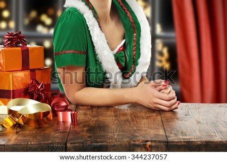 brown wooden table and green elf and box of gifts  - stock photo