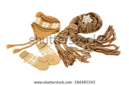 Brown wool scarf, a pair of mittens and a hat nicely arranged. Winter accessories isolated on white background. - stock photo