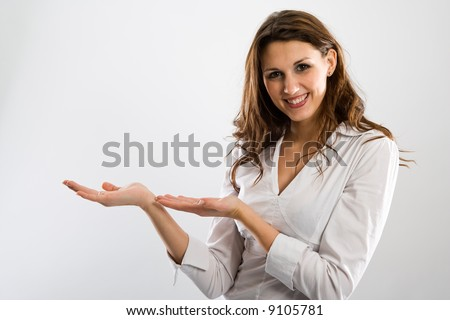 Brownhaired beauty holding both hands beside her to present something while smiling. - stock photo