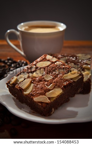 brownie cake and hot coffee on wood table - stock photo