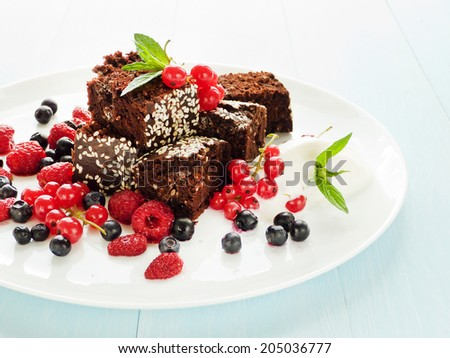 Brownies with chocolate chips, sesame seed, berries and ice cream. Shallow dof. - stock photo