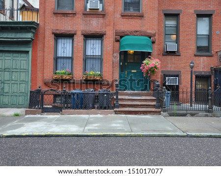 Brownstone Home with Green Awning Pink Petunias and Trash Cans lined up behind rod iron fence in Brooklyn New York USA - stock photo
