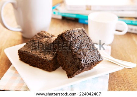 browny cake ready to eat on white dish with coffee cup and magazine book on table top - stock photo