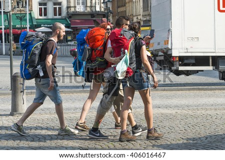 BRUGES, BELGIUM - JULY 3, 2015: A group of tourists backpacking, roam the streets of the historic center of the city. - stock photo
