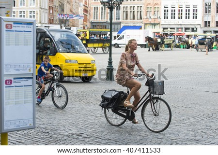 BRUGES, BELGIUM - JULY 3, 2015: A woman riding her bicycle passes through one of the streets of the old town. - stock photo