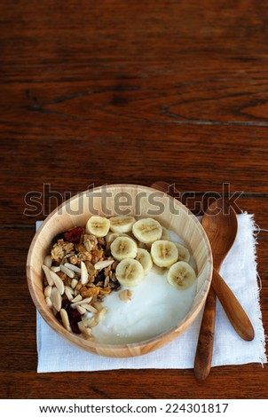 brunch : home made yogurt with granola and banana in wooden bowl.  - stock photo