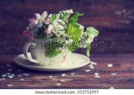 brunch of blossom flowers in a cup on wooden background - stock photo