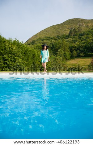 brunette adult woman with black hat and green dress looking at camera standing walking barefoot next to big blue swimming pool with trees, nature and mountain around - stock photo