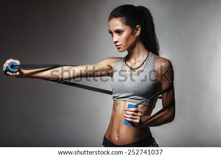 brunette athletic woman exercising with rubber tape - stock photo