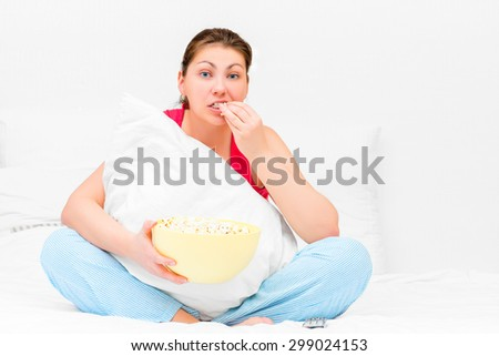 Brunette attentively watching television and eating popcorn - stock photo