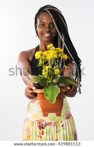 Brunette beautiful woman, with braided hair, offering yellow flowers and smiling, in a white background. - stock photo