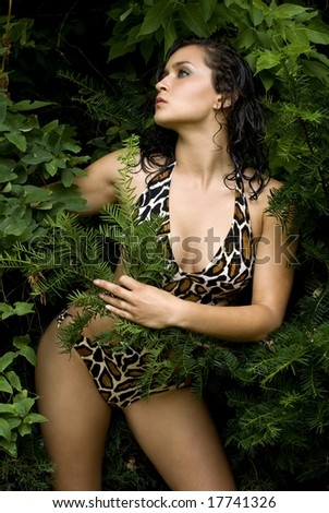 Brunette beauty in animal print bathing suit holding green leaves on a sunny day - stock photo