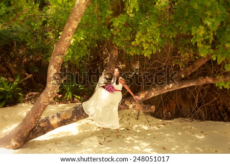 brunette bride in long white wedding dress and bridal bouquet sitting on the big tree on island beach in Thailand - stock photo
