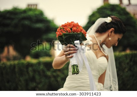 Brunette bride with wedding bouquet on hand - stock photo