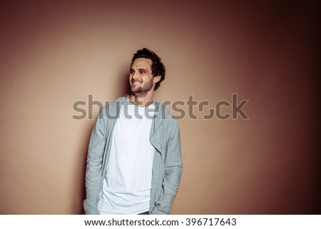 Brunette brown haired man with beard and white t-shirt and grey hoody in front of beige studio backdrop - stock photo