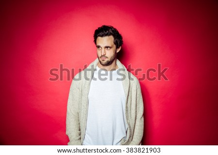 Brunette brown haired man with beard and white t-shirt and red hoody in front of beige studio backdrop - stock photo