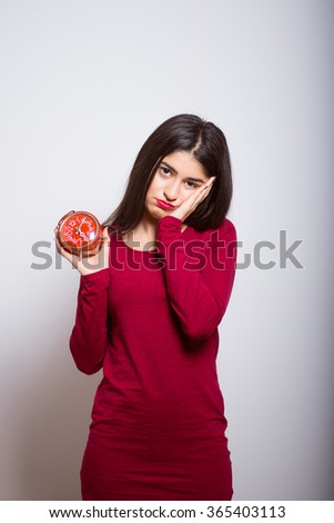 Brunette business girl sleeps with an alarm clock in a red dress, studio isolated portrait emotions - stock photo