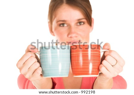 Brunette business woman in  an informal light pink shirt.  Holding two cups.  Shallow depth-of-field - cups in focus, face out of focus. - stock photo