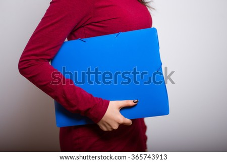 Brunette business woman with a folder of documents in a red dress, studio isolated portrait emotions - stock photo