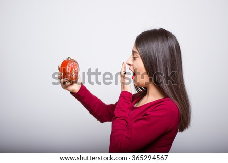 brunette business woman yawning with an alarm clock in a red dress, studio isolated portrait emotions - stock photo