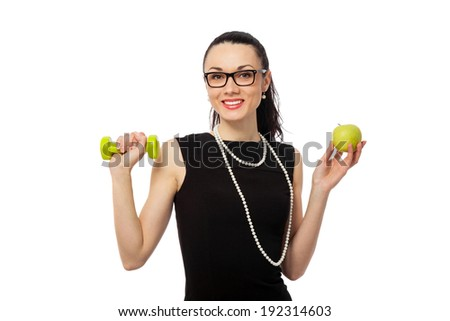 brunette businesswoman in black dress holding apple and dumbbells over white background. healthy lifestyle  - stock photo