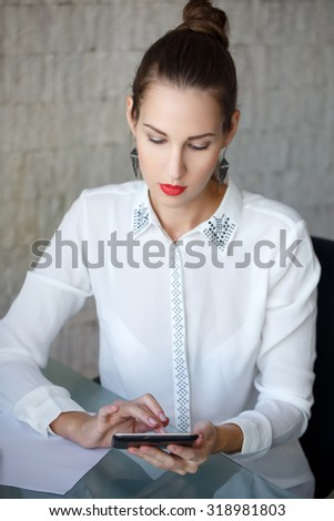 Brunette businesswoman using tablet in office - stock photo