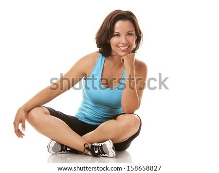 brunette caucasian fitness model  sitting down on white background - stock photo