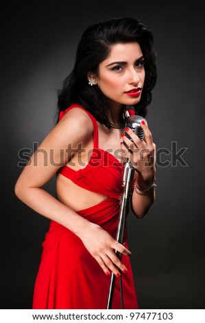 Brunette chanteuse in a vintage red dress - stock photo