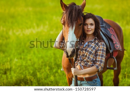 brunette cowgirl woman posing with horse outdoors portrait - stock photo