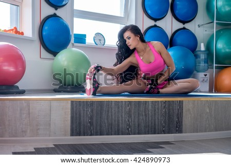 Brunette doing stretching exercise in fitness room - stock photo
