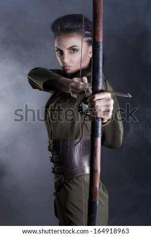 brunette elf with bow in hand on gray background - stock photo