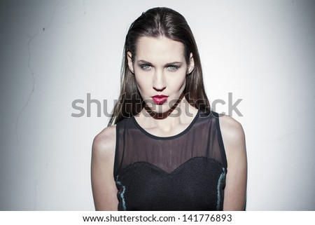 Brunette fashion model in dark dress posing at wall - stock photo