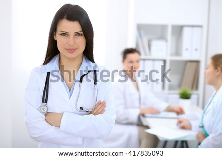 Brunette female doctor on the background of colleagues talking to each other in hospital - stock photo